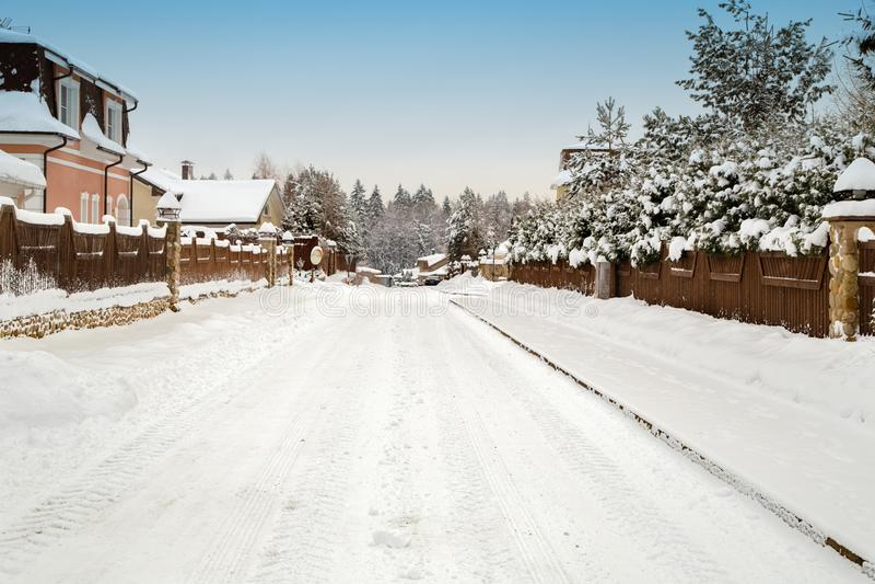 Estrada nevado entre casas de campo imagens de stock royalty free