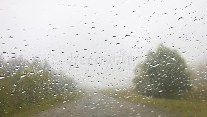 Estrada no tempo nebuloso chuvoso atrav?s do para-brisa do carro imagem de stock royalty free