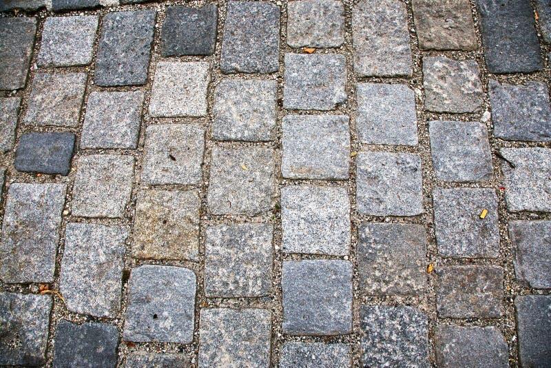 Estrada pavimentada com pedras de pavimenta??o Cobbles o fundo fotografia de stock royalty free