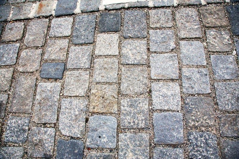 Estrada pavimentada com pedras de pavimenta??o Cobbles o fundo fotos de stock royalty free
