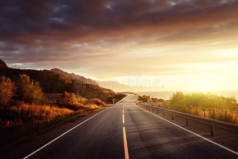 Estrada pelo mar no tempo do nascer do sol, ilha de Lofoten, Noruega imagem de stock