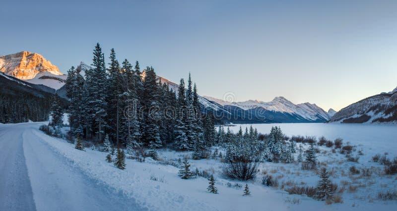 Estrada pequena e vazia do inverno, com uma floresta pequena e um lago congelado grande durante o por do sol em montanhas bonitas fotografia de stock