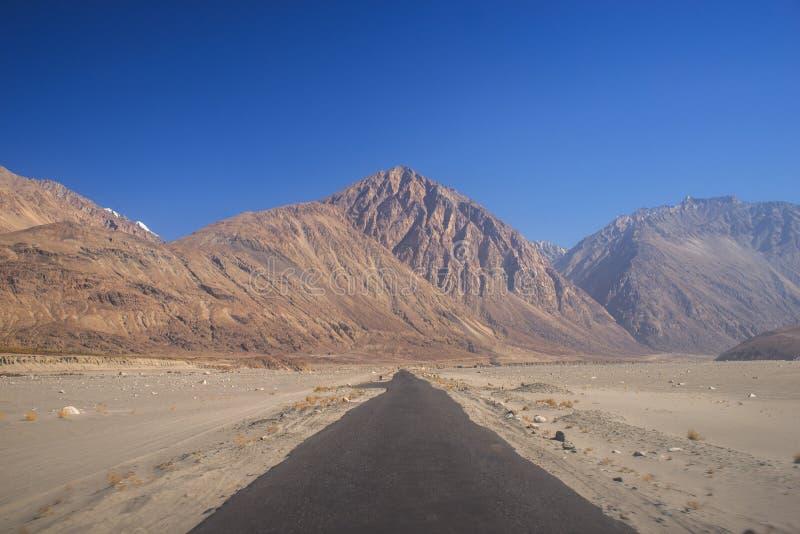 Estrada preta reta às montanhas foto de stock