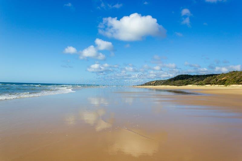 A estrada principal do transporte em Fraser Island - costa molhada larga da praia da areia que enfrenta o Oceano Pac?fico - 75 mi imagem de stock