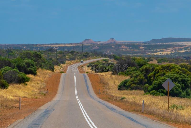 Estrada que conduz sobre montes pequenos na paisagem australiana do arbusto durante a mola fotos de stock