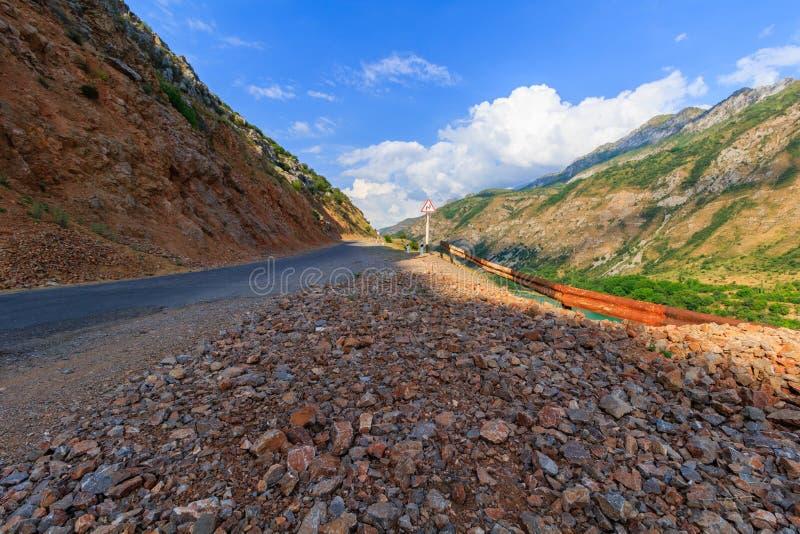 A estrada quebrada nas montanhas e a curvatura perigosa assinam fotografia de stock royalty free