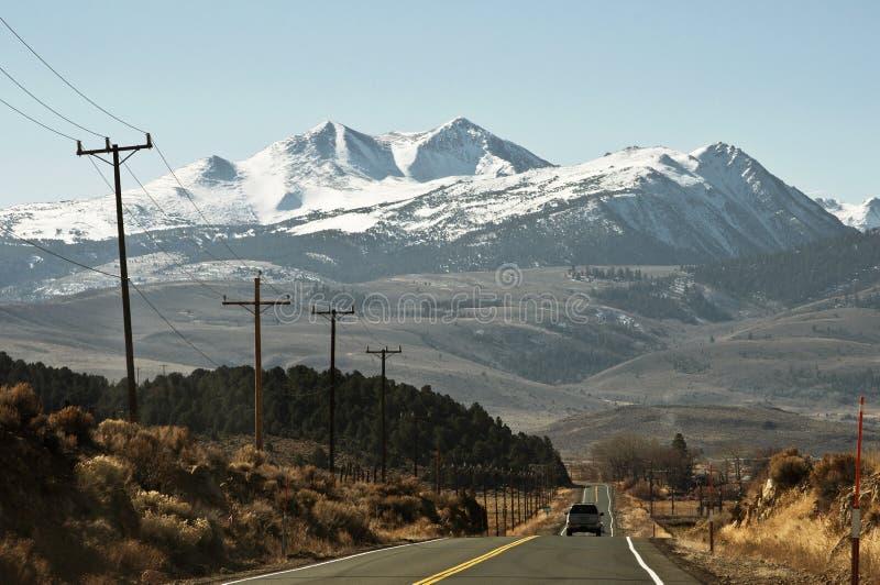 Estrada reta às montanhas foto de stock