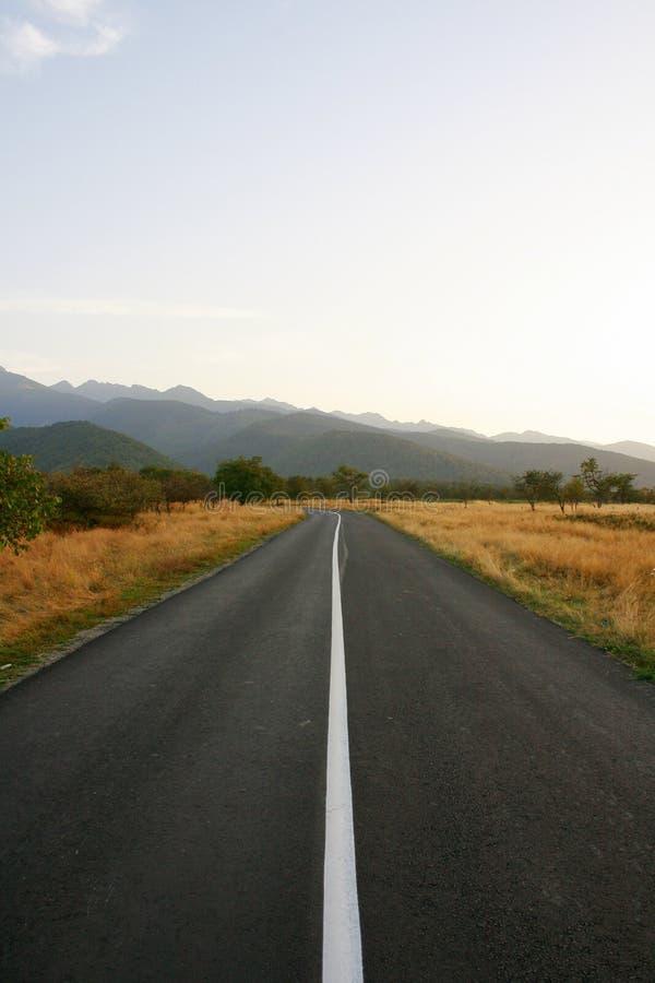 Estrada reta às montanhas na noite imagens de stock
