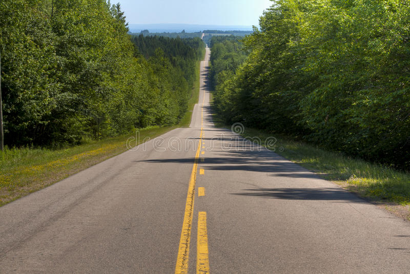 Estrada reta longa através de Hilly Terrain fotos de stock royalty free
