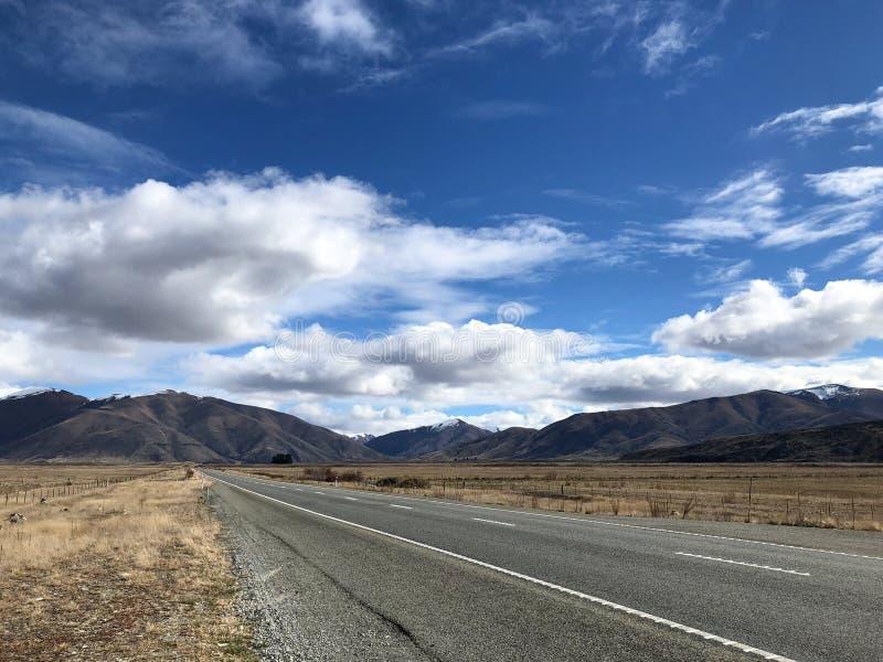 Estrada reta que conduz às montanhas e às nuvens azuis do céu e as brancas foto de stock