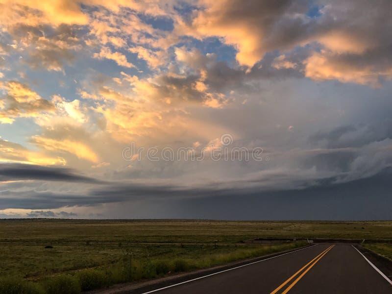 Estrada reta que conduz ao por do sol imagens de stock royalty free