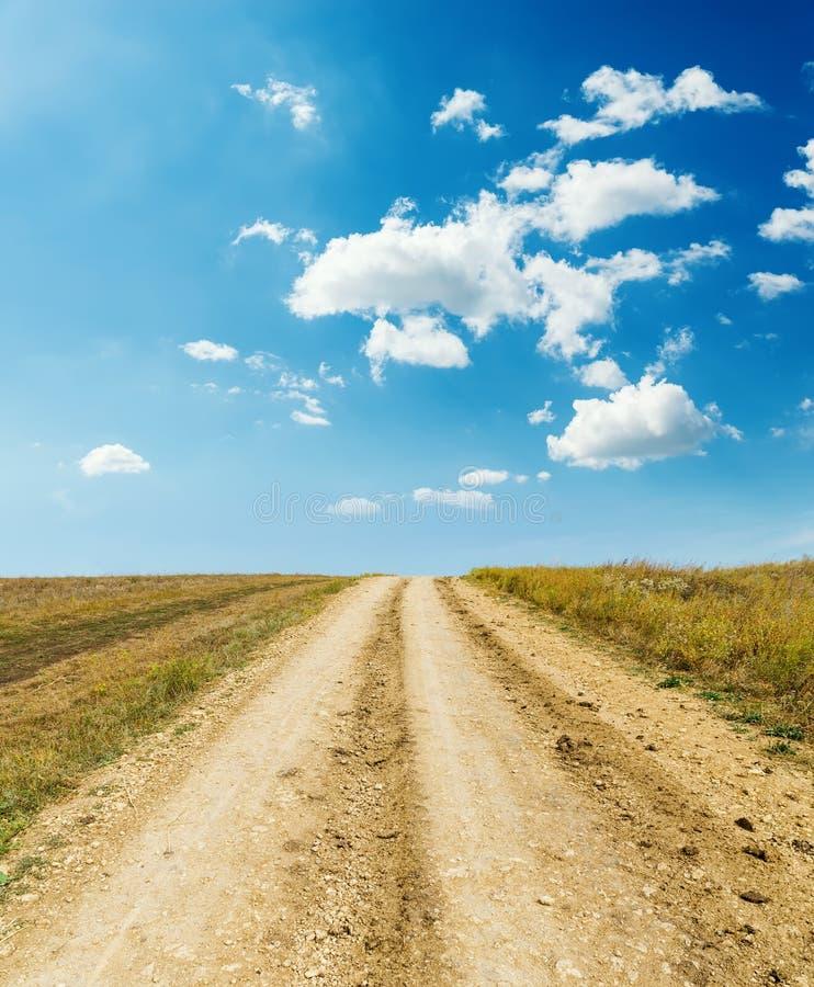 Estrada rural ao horizonte e às nuvens imagens de stock