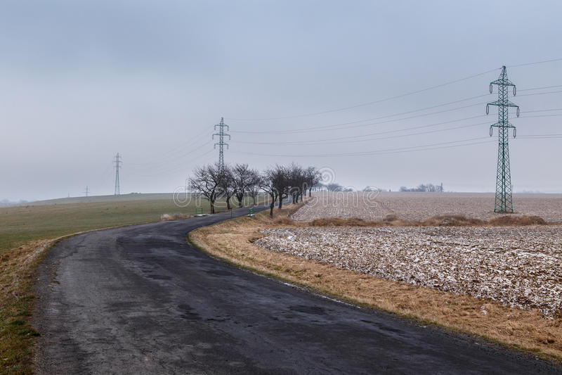 Estrada rural através de um campo coberto com a geada foto de stock