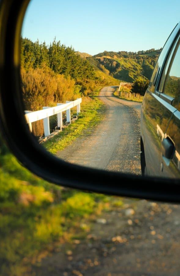 Estrada rural Metalled com a cerca do bastão e de fio, vista no espelho de asa de um carro, península de Mahia, ilha norte, Nova  imagem de stock