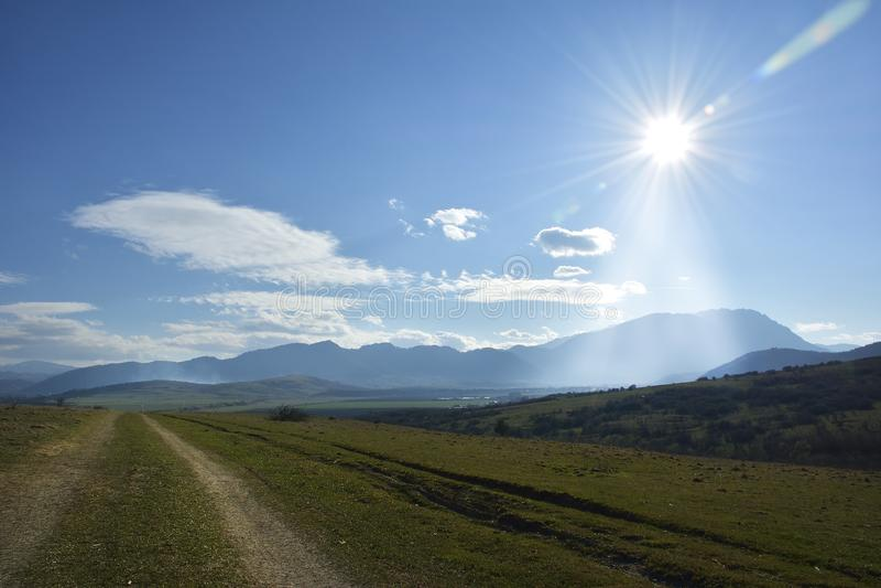 A estrada rural, o céu azul e o sol fotografia de stock royalty free