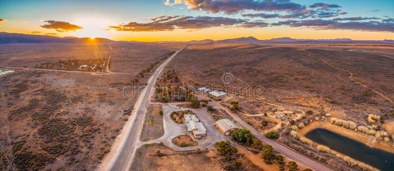 Estrada rural que conduz ao horizonte no por do sol imagens de stock