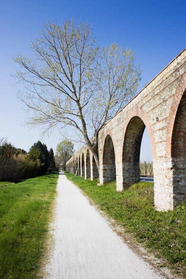 Estrada secundária ao longo de um aqueduto romano fotos de stock