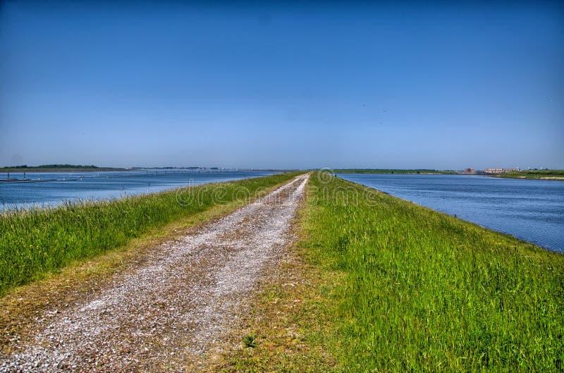 Estrada secundária cercada pela água na Holanda, Países Baixos, HDR imagens de stock royalty free