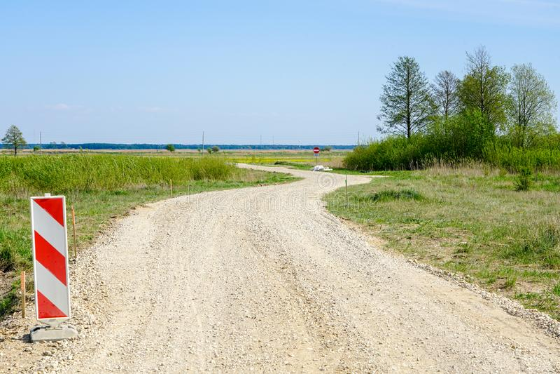 Estrada secundária rural de enrolamento, sinal de aviso no primeiro plano imagens de stock royalty free