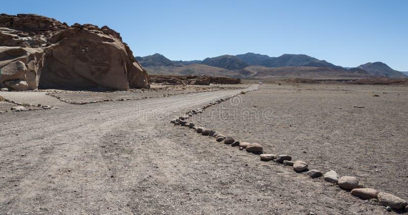 Estrada Unpaved perto dos Petroglyphs antigos nas rochas em Yerbas Buenas no deserto de Atacama no Chile fotos de stock royalty free