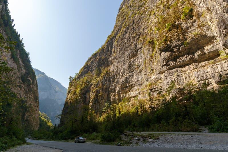 A estrada vai entre os penhascos O carro do turista é estacionado no freio da estrada fotos de stock
