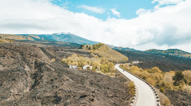 Estrada vazia ao vulcão de Etna que pode ser visto no horizonte fotos de stock royalty free