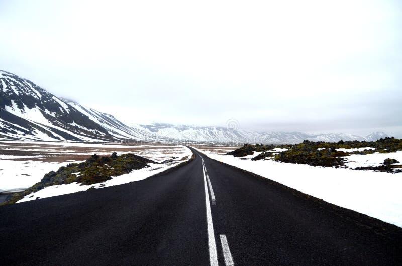 Estrada vazia através da neve e das montanhas imagens de stock royalty free