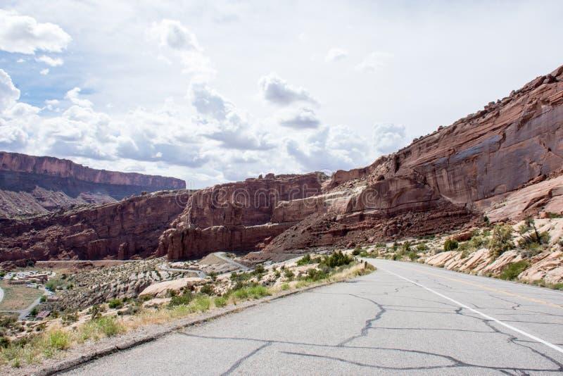 Estrada vazia através do parque nacional dos arcos em Utá em um dia em parte nebuloso fotografia de stock royalty free