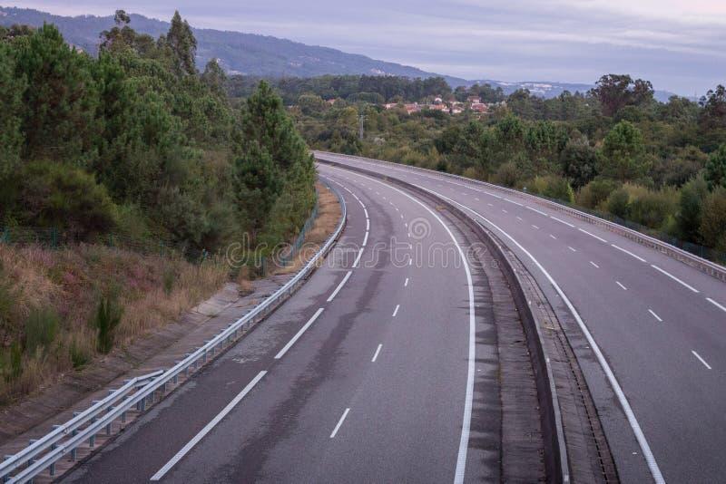 Estrada vazia larga com a curva na manhã Curso e fundo do destino Estrada asfaltada livre com fundo da montanha imagem de stock