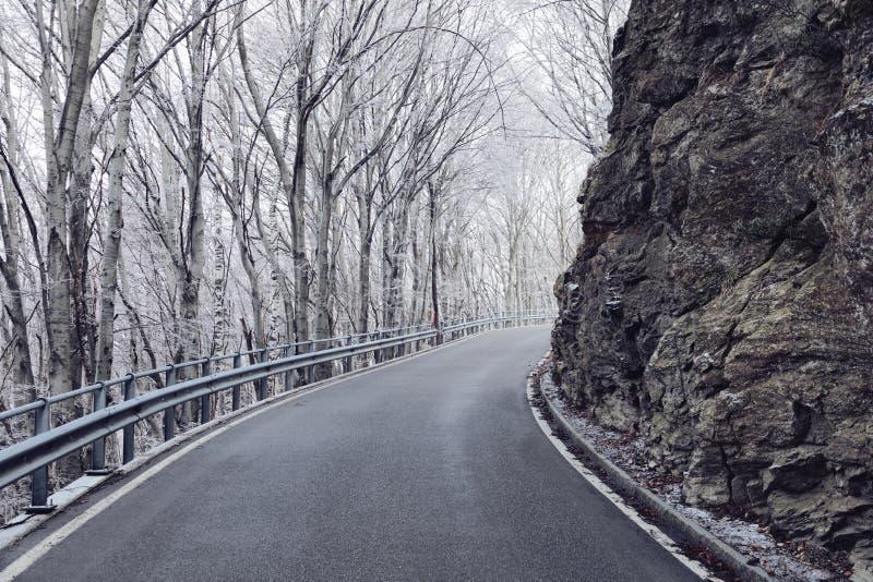 Estrada vazia no inverno, rocha da montanha na borda da estrada imagens de stock royalty free