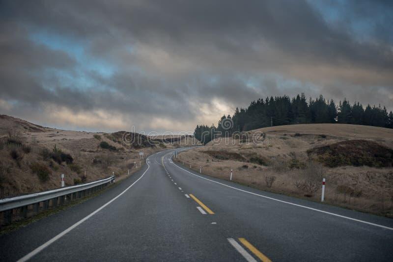 Estrada vazia que curva-se à direita no crepúsculo fotografia de stock royalty free