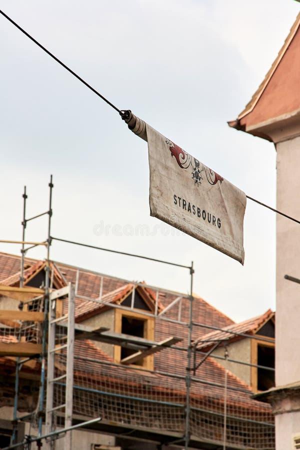 Estrasburgo, Francia - 15 de junio de 2010: Una bandera combinada con la inscripción Estrasburgo en la ciudad vieja de Estrasburg imagen de archivo