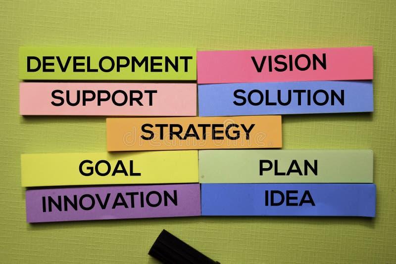 Estratégia, desenvolvimento, apoio, visão, solução, objetivo, plano, ideia, texto da inovação nas notas pegajosas isoladas na mes imagens de stock
