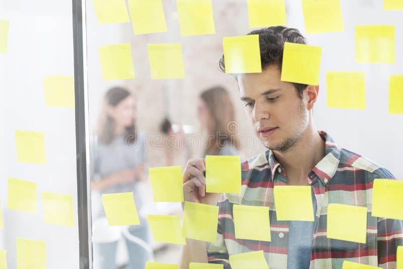 Estratégias novas da escrita do homem de negócios em notas adesivas foto de stock royalty free