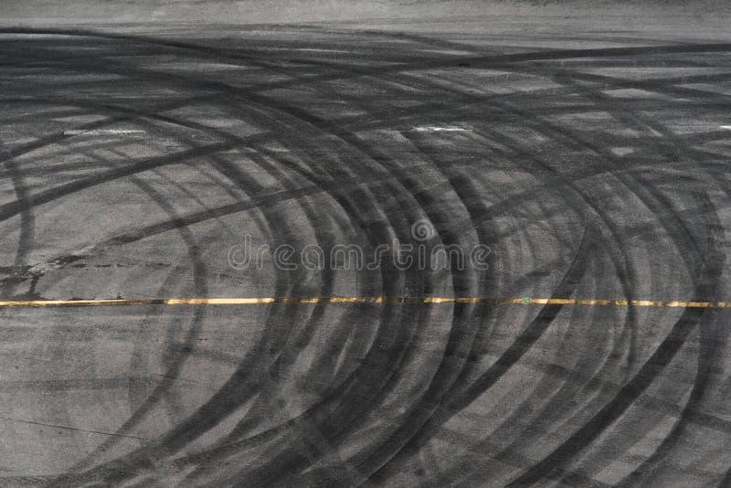 Estratto delle ruote nere della gomma causate in macchina della deriva sulla strada fotografie stock libere da diritti