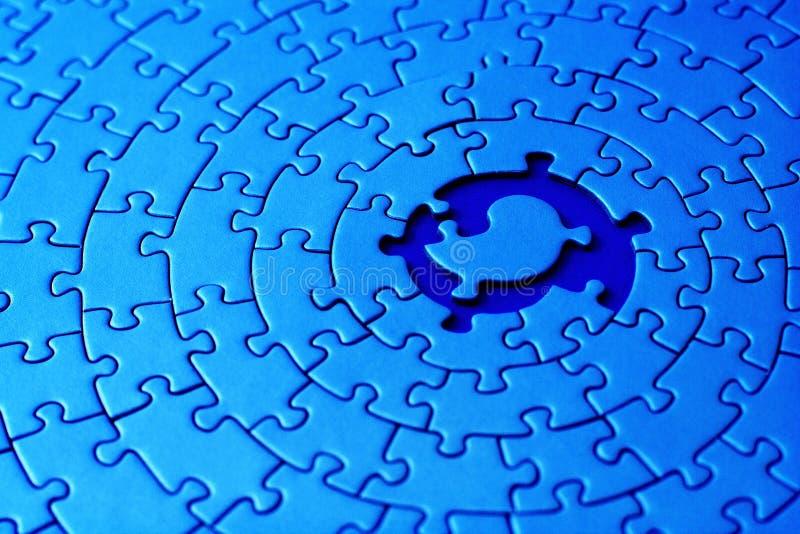 Estratto di un jigsaw blu con spazio e di una delle parti mancanti nel centro immagine stock libera da diritti