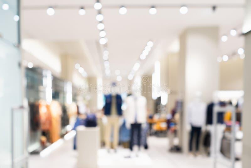 Estratto vago dell'interno del boutique del negozio di vestiti di modo nel centro commerciale, con il fondo leggero del bokeh Imm fotografia stock