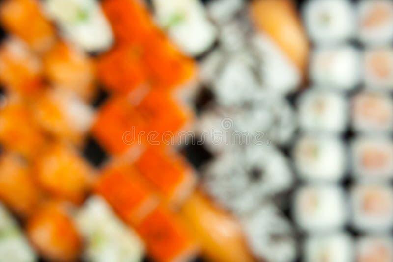 estratto vago Senza cuciture avvolto defocused fine sull'insieme delizioso succoso fresco dei sushi Vista superiore immagine stock libera da diritti