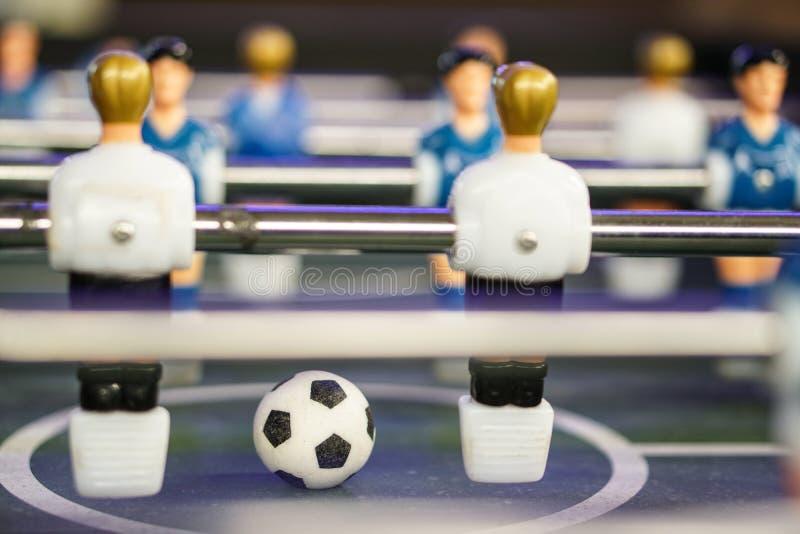 Estrattore a scatto del gioco di calcio di calcio-balilla Palla di calcio sul campo da gioco immagini stock