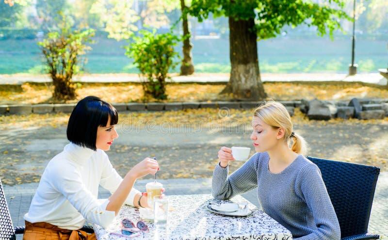 Estrechas relaciones amistosas de la amistad verdadera Confíela en Los amigos femeninos se sientan en cafetería y disfrutan de ch fotografía de archivo libre de regalías