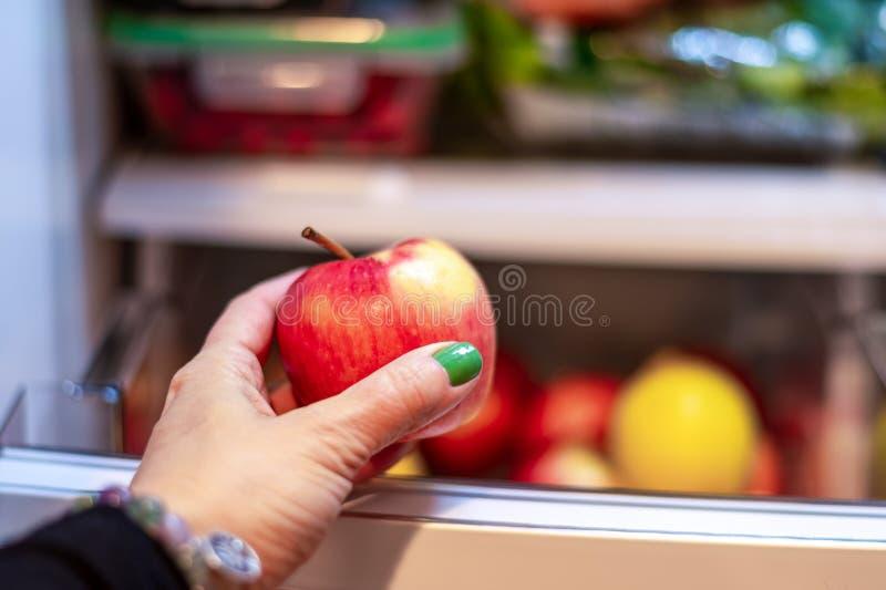 Estreita a mão da mulher tirando uma maçã da geladeira foto de stock