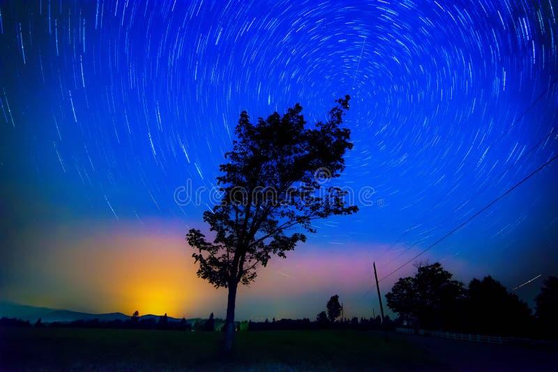 A estrela arrasta, o fogo voa e aurora boreal sobre a exploração agrícola fotos de stock