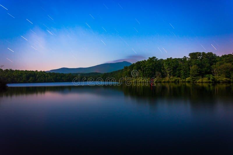 A estrela arrasta sobre Julian Price Lake na noite, ao longo do Ridg azul foto de stock royalty free