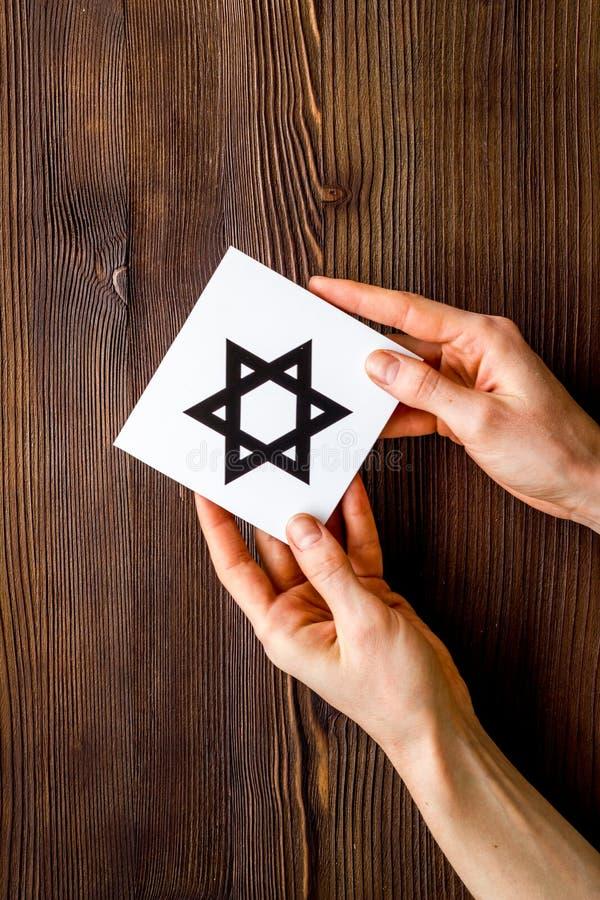 Estrela de David em mãos - símbolo religioso do Judaísmo - na mesa de madeira imagens de stock royalty free