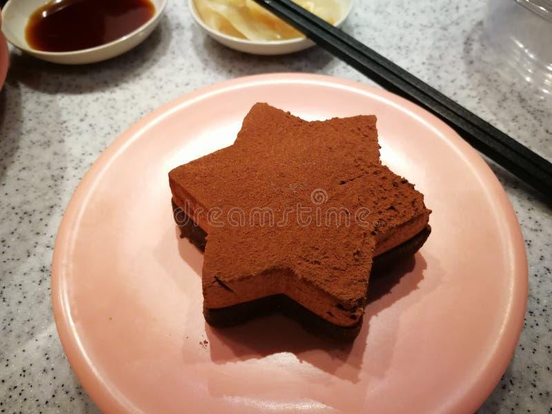 A estrela deu forma ao bolo de chocolate, polvilhado com o pó de cacau imagem de stock