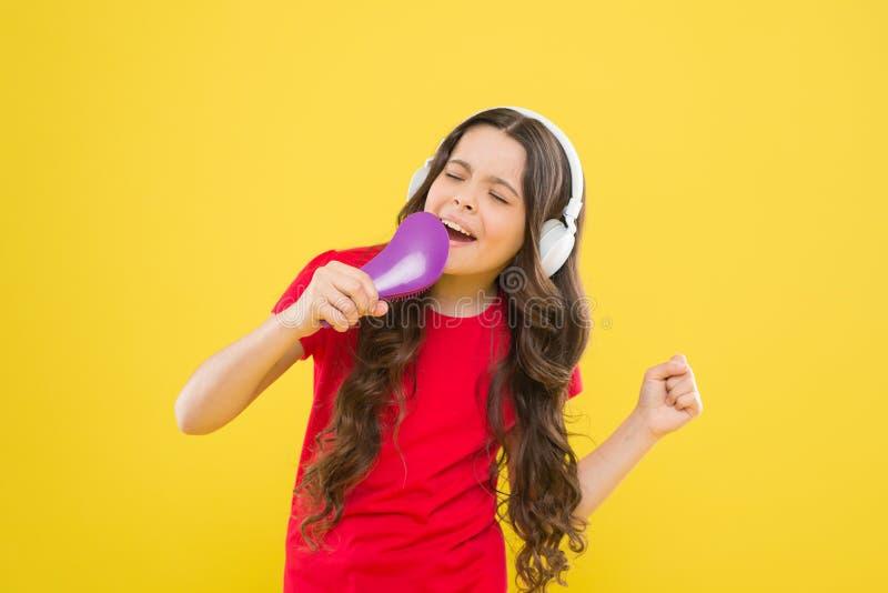 Estrela do karaoke Menina bonito que finge o karaoke do canto no fundo amarelo Criança adorável que executa a música do karaoke foto de stock royalty free