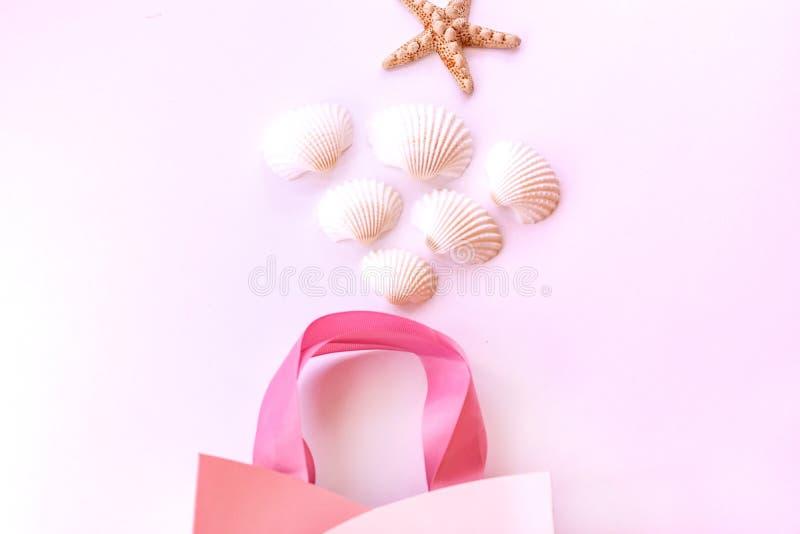 Estrela do mar, conchas do mar e saco do presente em um fundo cor-de-rosa delicado Fundo do ver?o imagem de stock royalty free