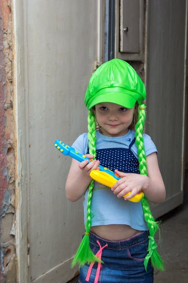 Estrela do rock da menina em uma peruca com guitarra fotos de stock