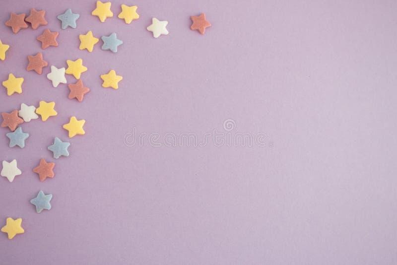 Estrelas coloridas no fundo roxo com espaço da cópia Cartão brilhante foto de stock