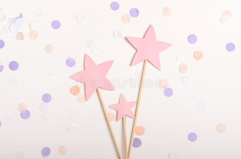 Estrelas cor-de-rosa em uma vara que cobre no fundo branco com confetes, cores pastel O feriado das crianças, ano novo Vista supe foto de stock royalty free